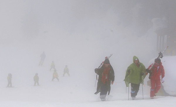 Skiers are are barely visible as they walk down the mountain as first training for the Men's Downhill was canceled due to poor visibility at the Vancouver 2010 Olympics in Whistler, British Columbia, Wednesday, Feb. 10, 2010.  (AP Photo/Sergey Ponomarev)