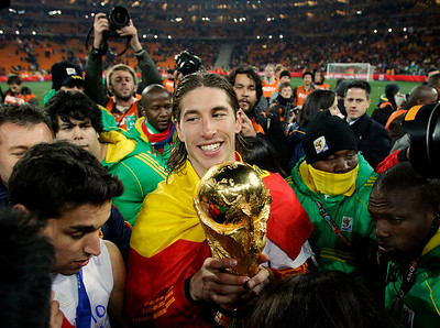 Spain's Sergio Ramos, center, holds the World Cup trophy as he celebrates following the World Cup final soccer match between the Netherlands and Spain at Soccer City in Johannesburg, South Africa,  Sunday, July 11, 2010.  (AP Photo/Ivan Sekretarev)