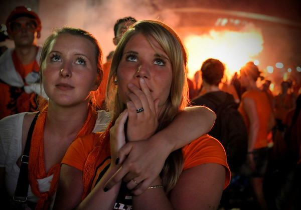 Dutch soccer fans, dressed in orange, react in downtown Amsterdam, Netherlands, Sunday, July 11, 2010 after their team lost the World Cup soccer final match being played in South Africa against Spain. (AP Photo/Bela Szandelszky)