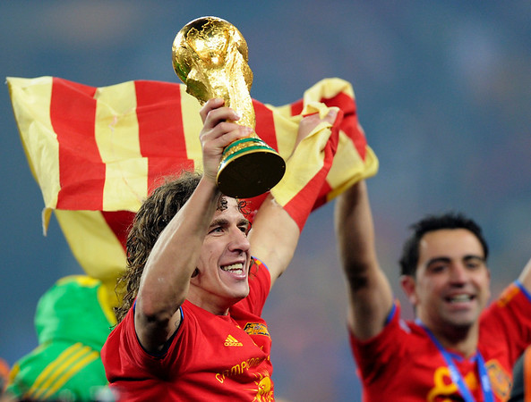 Spain's Carles Puyol, left, holds up the World Cup trophy as he celebrates with Spain's Xavi Hernandez, right, following the World Cup final soccer match between the Netherlands and Spain at Soccer City in Johannesburg, South Africa, on Sunday, July 11, 2010.  (AP Photo/Dani Ochoa de Olza)