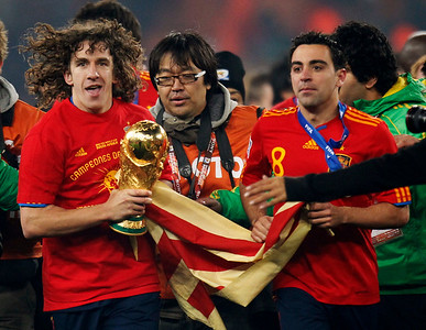 Spain's Carles Puyol, left, runs with the World Cup trophy, followed by Spain's Xavi Hernandez, right, as they celebrate following the World Cup final soccer match between the Netherlands and Spain at Soccer City in Johannesburg, South Africa, Sunday, July 11, 2010.  (AP Photo/Luca Bruno)