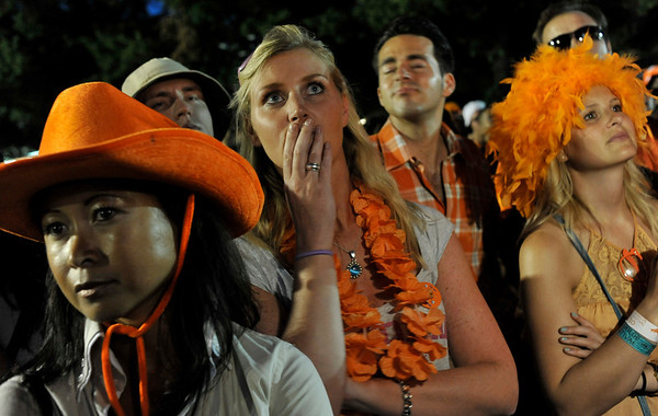Dutch soccer fans, dressed in orange, react in downtown Amsterdam, Netherlands, Sunday, July 11, 2010 after their team lost the World Cup soccer final match against Spain which was being played in South Africa. . (AP Photo/Bela Szandelszky)