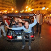 Two young Egyptian soccer fans celebrate from the back of a moving vehicle cruising the streets after their team beat Ghana 1-0 to win the African Cup of Nations soccer final for the third time in a row in a match played in Luanda, Angola, in Tahrir square in downtown Cairo, Egypt, on Sunday. (AP Photo/Ben Curtis)