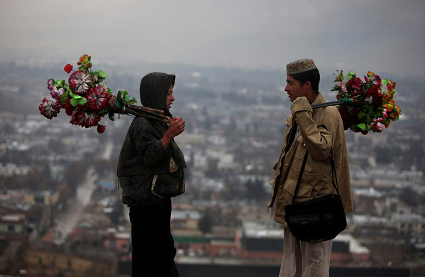 Afghan artificial flower vendors, Hikmat, right, and Saddam, left, speak on a hilltop as the city of Kabul is seen in the background on a rainy day in Kabul, Afghanistan, on Thursday. Major world powers opened talks Thursday seeking an end to the grinding conflict in Afghanistan, drafting plans to hand over security responsibilities to local forces and quell the insurgency with an offer of jobs and housing to lure Taliban fighters to renounce violence. (AP Photo/Altaf Qadri)