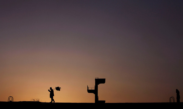 An Afghan artificial flower seller is silhouetted against the setting sun as he walks on the parapet of an unfinished Soviet-era swimming pool in Kabul, Afghanistan, on Monday, Feb. 1, 2010. (AP Photo/Altaf Qadri)