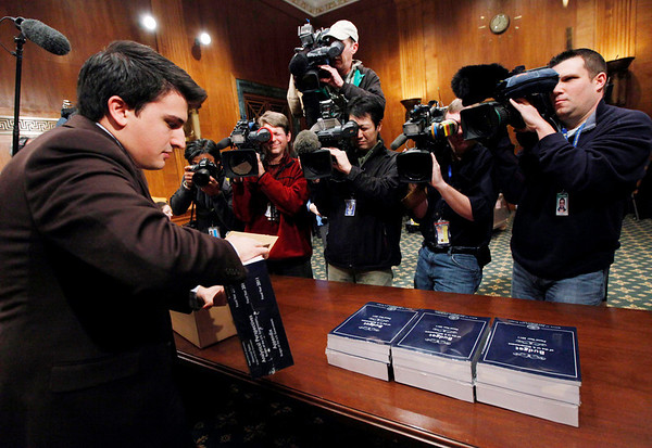 Senate staff memeber Sam Armocido, piles copies of President Barack Obama's budget delivered to the Senate Budget Committee on Capitol  Hill in Washington on Monday, Feb. 1, 2010.  (AP Photo/Manuel Balce Ceneta)
