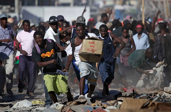 A man runs with a box during sporadic looting in the aftermath of the Jan. 12 earthquake in Port-au-Prince, Haiti, on Thursday. (AP Photo/Ariana Cubillos)