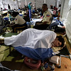 Two Haitian police officers sit next to Charisa Coulter, 24, of Boise, Idaho, one of the 10 Americans who were arrested while trying to bus children out of Haiti without proper documents or government  permission, as she rests on a cot at the University of Miami's field hospital, near Port-au-Prince's international airport, Monday, Feb. 1, 2010. Coulter, who's diabetic, initially thought her insulin had gone bad in the heat but now she's being treated for what she said is either severe dehydration or the flu. (AP Photo/Ariana Cubillos)