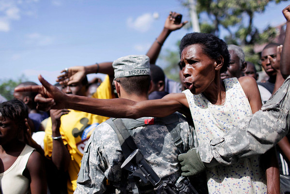 A woman asks for food as US Army soldiers of the 82nd Airborne Division stand guard during the distribution of bags with rice by the Christian NGO World Vision International in the aftermath of the Jan. 12 earthquake in Port-au-Prince on Sunday.(AP  Photo/ Ariana Cubillos)