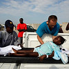 Paramedic Tim Mosher, of Troytown, Ohio, place five-year-old Betina Joseph on a stretcher before being driven to a private jet for her evacuation to Children's Hospital in Philadelphia by the Boston-based aid group Partners in Health from Port-au-Prince on Sunday. Doctors skirted a bureaucratic logjam to save the life of Joseph, who developed tetanus from a small cut on her thigh, and two more critically ill children, victims of Haiti's earthquake, flying them to U.S. hospitals on a private jet to avoid a military suspension of medical evacuation flights. (AP Photo/Andres Leighton)