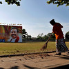 A Sri Lankan worker sweeps a street in the backdrop of an election campaign billboard of Sri Lankan President Mahinda Rajapaksa in Colombo, Sri Lanka, on Thursday. Rajapaksa swept to a second term in office, but his rival cried foul and the opposition said it will challenge the results in court. (AP Photo/Eranga Jayawardena)