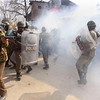 An Indian police officer, left, prepares to fire tear a gas shell as Indian paramilitary soldiers run for cover from shells thrown back at them by Kashmiri Muslim protesters, unseen, during a protest in Srinagar, India, on Monday, Feb. 1, 2010. Rock-throwing protesters clashed with government forces in Indian-controlled Kashmir on Monday, a day after a police-fired tear gas shell struck and killed a boy. (AP Photo/ Dar Yasin)