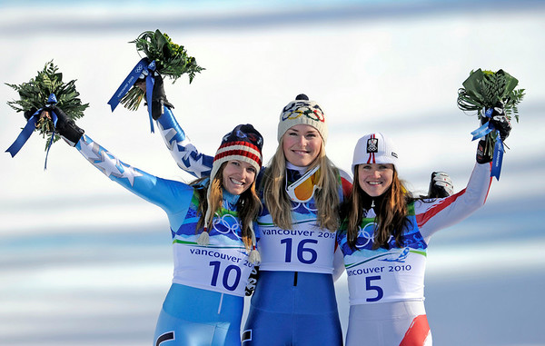 Lindsey Vonn of the United States, the gold medal winner, center, celebrates with her compatriot Julia Mancuso, silver,  left, and Austria's bronze medalist Elisabeth Goergl during the flower ceremony for the Women's downhill at the Vancouver 2010 Olympics in Whistler, British Columbia, Wednesday, Feb. 17, 2010. (AP Photo/Gero Breloer)