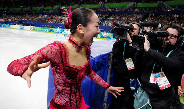 Japan's Mao Asada, left, reacts after performing her short program during the women's figure skating competition at the Vancouver 2010 Olympics in Vancouver, British Columbia, Tuesday, Feb. 23, 2010. (AP Photo/Mark Baker)