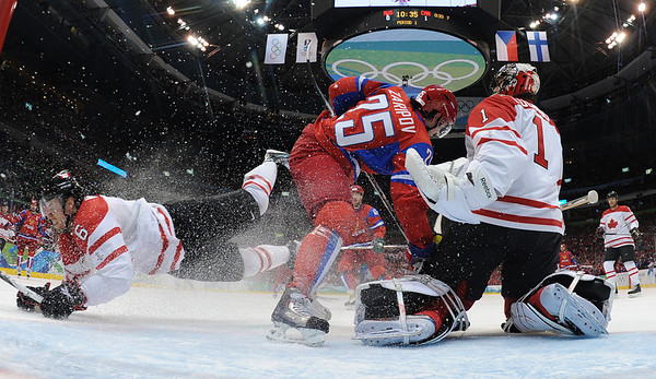 Canada's Shea Weber (6) falls as defends the goal with goalie Roberto Luongo (1) in the first period in a men's quarterfinal round ice hockey game at the Vancouver 2010 Olympics in Vancouver, British Columbia, Wednesday, Feb. 24, 2010. Russia's Danis Zaripov (25) positions himself in front of Luongo. Canada won 7-3. (AP Photo/Bruce Bennett, Pool)