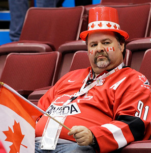 A fan stays in his seat after a men's preliminary round ice hockey game between USA and Canada at the Vancouver 2010 Olympics in Vancouver, British Columbia, Sunday, Feb. 21, 2010. (AP Photo/Chris O'Meara)
