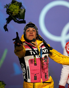 Germany's gold medal winner Magdalena Neuner  throws her flowers into the crowd during the medal ceremony for the Women's 12.5k mass start Biathlon race at the Vancouver 2010 Olympics in Whistler, British Columbia, Canada, Sunday, Feb. 21, 2010. (AP Photo/Matthias Schrader)