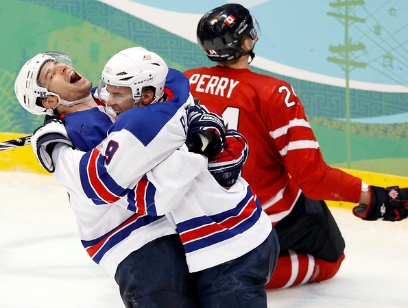 Team USA's Ryan Kessler, left, and Zach Parise (9) celebrate as Canada's  Coery Perry kneels in the background during third period men's ice hockey action Sunday, Feb. 21, 2010 at the 2010 Winter Olympic  Games in Vancouver, British Columbia. USA won 5-3. (AP Photo/The Canadian Press, Ryan Remiorz)