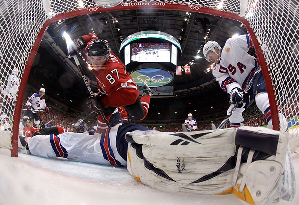 Canada's Sidney Crosby (87) crashes over USA's goalie Ryan Miller (39) in the third period in a preliminary round men's ice hockey game at the Vancouver 2010 Olympics in Vancouver, British Columbia, Sunday, Feb. 21, 2010. The USA won 5-3. (AP Photo/Julie Jacobson)
