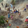 Pakistani villagers chase to relief supplies dropped from an army helicopter in a heavy flood-hit area of Mithan Kot, in central Pakistan, Monday, Aug. 9, 2010. The government has struggled to cope with the scale of the disaster, which has killed at least 1,500 people, prompting the international community to help by donating tens of millions of dollars and providing relief supplies. (AP Photo/Khalid Tanveer)