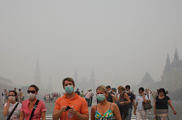 Tourists with face masks walk along  Red Square in a thick blanket of smog, in Moscow, Russia, Monday, Aug. 9, 2010. The Russian capital's chief health official reportedly says the number of deaths in Moscow is twice as high as usual because of smog suffocating the city from ongoing wildfires nearby. The Interfax news agency quotes Andrei Seltsovky on Monday as saying there are now 1,300 bodies in city morgues, which have a 1,500 capacity. (AP Photo/Alexander Zemlianichenko)