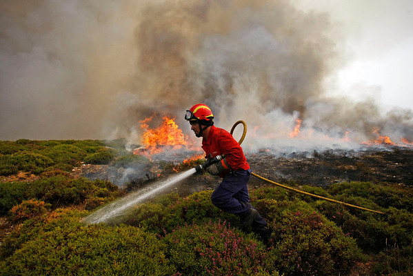A firefighter works on a fire front on the Arada mountain near Sao Pedro do Sul, northern Portugal, Monday, Aug. 9, 2010. Firefighters in Portugal were continuing to battle raging brush fires on Monday - they say some have been contained, but others are still burning out of control. (AP Photo/Francisco Seco)