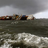 The Panamanian-registered container ship MSC Chitra that had Saturday collided with the MV-Khalijia-II, a St. Kitts registered ship, tilts in the Arabian Sea, close to Mumbai, India, Monday, Aug. 9, 2010. Indian coast guard ships and helicopters are working to try and contain an oil spill from the dangerously tilting container ship following the collision near Mumbai, a spokesman for India's defense ministry said Monday. (AP Photo/Rafiq Maqbool)