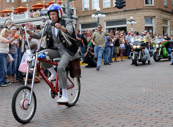 "Comedian Paul Ruebens, in character as Pee-wee Herman, leads 300 bikers out of Deadwood, S.D. on Monday, Aug. 9, 2010, on the 3rd Annual Legends Ride charity event during the 70th Annual Sturgis Motorcycle Rally. Reubens was slated to participate in various charity events and host what was billed as the world's largest ""Tequila dance"" to the tune of the 1958 instrumental by the Champs. (AP Photo/Steve McEnroe)"