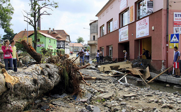 Residents stand in a  destroyed  street after flash floods in the town of Bogatynia, Poland, Monday , Aug. 9, 2010. The flooding has struck an area near the borders with Germany and the Czech Republic, where there have also been several fatalities. (AP Photo/Robert  Steiner )