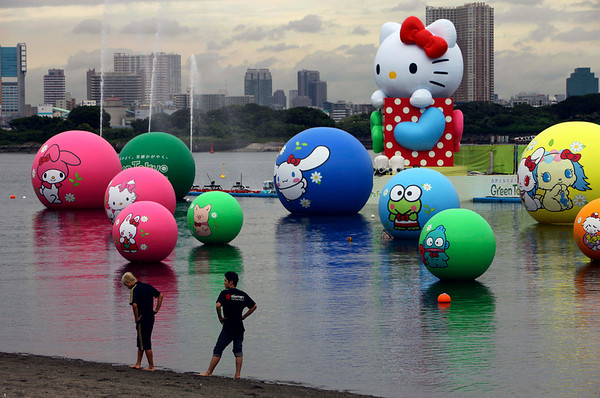"Boys stroll on the beach with the backdrop of the 8-meter (26 foot 3 inch)-tall ""Hello Kitty"" balloon floating in the waters together with other popular character-featured balls in Tokyo, Monday, Aug. 9, 2010. A summer event kicks off to raise fund for a tree-planting campaign in Tokyo, supported by Japan's gift and mascot products maker Sanrio Co., which produces Hello Kitty. (AP Photo/Junji Kurokawa)"