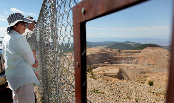 "Laura Moncrief of Divide peers though the fence overseeing the Cresson open-pit surface mine Sunday, July 18, 2010 in Victor, Colo. during a guided tour of the town's historical mining structures.    Three hundred hours, $700 and multiple field trips later, Steve Veatch and his club fellows had compiled a historical record of Victor which a local geologist hails as ""the best single source"" for detailed information on the town.(AP Photo/The Gazette, Anthony Souffle)"