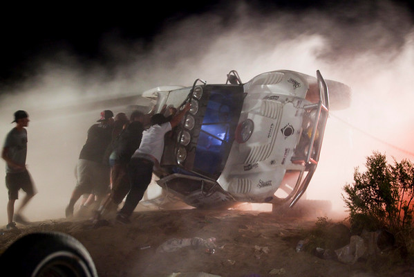 Workers push an overturned off-road race truck upright Sunday, Aug. 15, 2010 after it went out of control and ran into a crowd of spectators during a race in Lucerne Valley, Calif., on Saturday. At least eight people were killed during the incident about 100 miles east of Los Angeles.(AP Photo/Francis Specker)