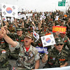 "South Korean Vietnam War veterans with the national flags shout slogans during a rally against North Korea on Korea's Liberation Day in front of Tongil bridge near the border village of the Panmunjom (DMZ) in Paju, South Korea, Aug. 15, 2010. South Korean President Lee Myung-bak urged North Korea to abandon military provocations and make a ""courageous change"" toward peace, using a speech Sunday marking the Korean peninsula's liberation from Japanese rule to outline a path for its eventual reunification. (AP Photo/Ahn Young-joon)"