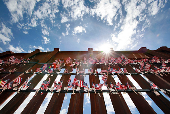 Flags hang on the International border wall Sunday, Aug. 15, 2010 in Hereford, Ariz. at a United Border Coalition Tea Party Rally. Conservative tea party activists gathered along a remote stretch of the Arizona-Mexico border about 70 miles (113 kilometers) west of Nogales.  (AP Photo/Matt York)