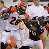Cincinnati Bengals running back Bernard Scott (28) is tackled by Denver Broncos cornerback Nate Jones (33) after a 48-yard run in the first half of an NFL preseason football game, Sunday, Aug. 15, 2010, in Cincinnati. (AP Photo/Ed Reinke)