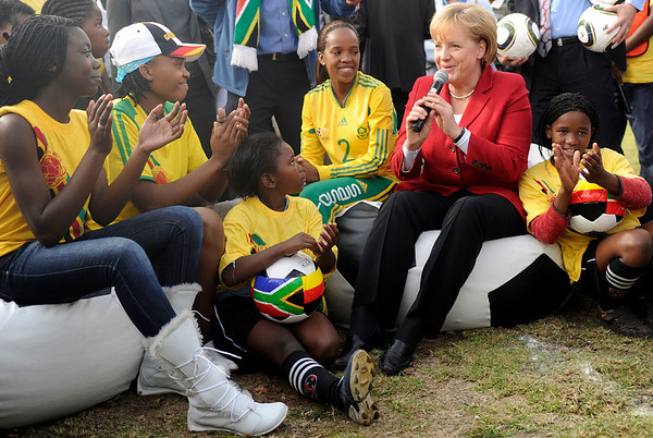 German Chancellor Angela Merkel, second right, meets with children and teenagers in the Township Khayelitsha near Cape Town, South Africa, on Saturday, July 3, 2010. Chancellor Merkel is in South Africa to visit the World Cup soccer match Germany versus Argentina at the Green Point Stadium later on Saturday. (AP Photo/ddp, Oliver Lang)