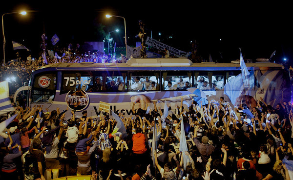 Supporters of Argentina's soccer team gather around the bus carrying the team's players to the Argentine Soccer Association (AFA) after being eliminated at the South Africa 2010 World Cup in Buenos Aires, Sunday July 4, 2010. (AP Photo/Natacha Pisarenko)