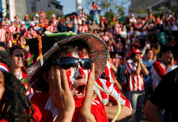A fan of Paraguay's soccer team watches the South Africa 2010 World Cup game between Paraguay and Spain on a screen in Asuncion, Saturday July 3, 2010. Spain won 1-0. (AP Photo/Jorge Saenz)
