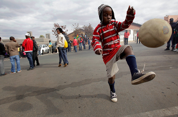 A young Soweto Township resident juggles a soccer ball as he awaits the arrival of the Ghana national soccer team, in Johannesburg, South Africa Sunday, July 4, 2010.  The Ghanaian team became the third African team ever to reach the World Cup quarterfinal round, where they were defeated by Uruguay. (AP Photo/Rebecca Blackwell)
