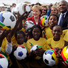 German Chancellor Angela Merkel, background center meets with children in the Township Khayelitsha near Cape Town, South Africa, on Saturday, July 3, 2010. Chancellor Merkel is in South Africa to visit the World Cup soccer match Germany versus Argentina at the Green Point Stadium later on Saturday. (AP Photo/ddp, Oliver Lang)