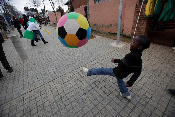 A young Soweto Township resident kicks a giant stuffed soccer ball as he awaits the arrival of the Ghana national soccer team, in Johannesburg, South Africa Sunday, July 4, 2010.  The Ghanaian team became the third African team ever to reach the World Cup quarterfinal round, where they were defeated by Uruguay. (AP Photo/Rebecca Blackwell)
