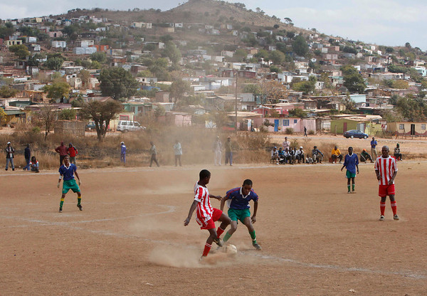 Amateur players play soccer at a Peace Cup Tournament in Attridgeville, South Africa, Saturday, July 3, 2010. The tournament, organized by the Catholic Church and running at the same time as the World Cup, is aimed to bring together fans of different social classes, ethnicity, and national origins  as well as fans from all over the world. (AP Photo/Denis Farrell)