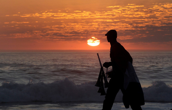 A beach vendor walks along the shore trying to sell the last of his World Cup souvenirs Sunday, July 4, 2010, in Cape Town, South Africa. (AP Photo/Julie Jacobson)