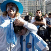 A fan of Argentina's soccer team holds his son crying after the 4-0 loss to Germany in a South Africa 2010 World Cup quarterfinal match, shown to the public on a giant screen in Buenos Aires, Saturday July 3, 2010. (AP Photo/Natacha Pisarenko)