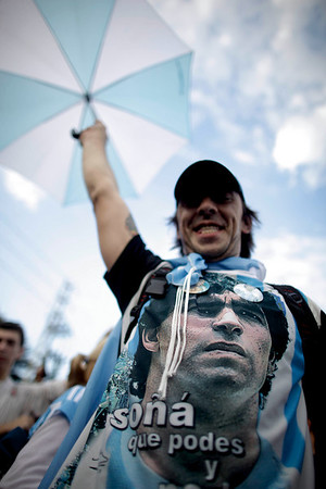 A fan of Argentina's soccer team waits for the arrival of its players after Argentina's elimination from the South Africa 2010 World Cup in Buenos Aires, Sunday July 4, 2010. The shirt shows an image of the team's coach Diego Maradona. (AP Photo/Natacha Pisarenko)