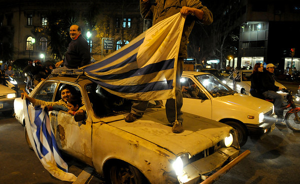 Fans of Uruguay's soccer team celebrate after Uruguay defeated Ghana at the South Africa 2010 World Cup, in Montevideo, Friday July 2, 2010.  Uruguay reached the World Cup semifinals for the first time since 1970, beating Ghana 4-2 on penalties after a 1-1 draw Friday.  (AP Photo/Matilde Campodonico)