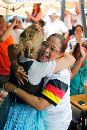 Carole Brendel, right, of Miami Beach, Fla., hugs a waitress at a German Restaurant in Miami Beach, after watching Germany defeat Argentina 4-0 in a World Cup quarterfinal soccer match, Saturday, July 3, 2010, in Miami Beach. (AP Photo/Wilfredo Lee)