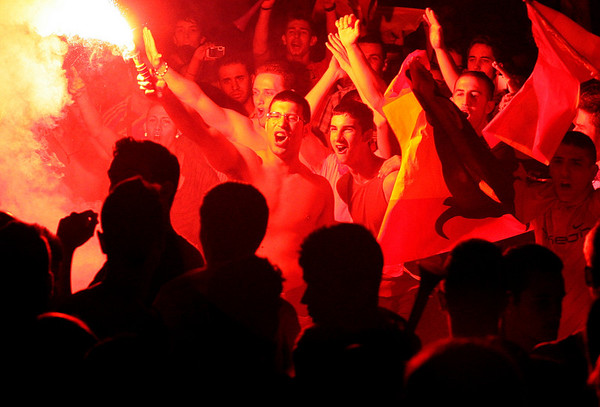 Fans react after Spain scored during the World Cup quarterfinal soccer match between Spain and Paraguay, watched on a large screen outside the Santiago Bernabeu stadium in Madrid, on Saturday, July 3, 2010.   Spain won 1-0. (AP Photo/Arturo Rodriguez)