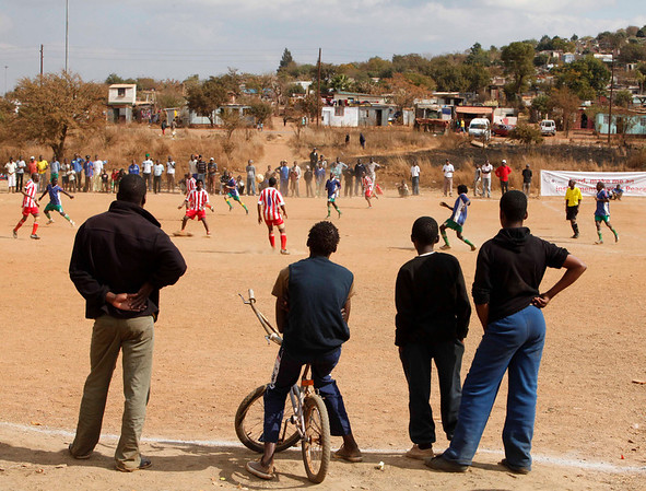 Soccer fans watch a soccer game by amateur soccer players at a Peace Cup Tournament in Attridgeville, South Africa, Saturday, July 3, 2010. The tournament, organized by the Catholic Church and running at the same time as the World Cup, is aimed to bring together fans of different social classes, ethnicity, and national origins as well as fans from all over the world. (AP Photo/Denis Farrell)