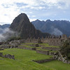 The Central Plaza of Machu Picchu as viewed from the Temple of the Three Windows. The Central Plaza's grassy field separates the Sacred Plaza and Intiwatana from the residential areas on the far side of the complex.  Huayna Picchu (aka 'Young Peak'), elevation 8924 feet, is in the background.  <br /> <br /> Machu Picchu, Cusco Region, Urubamba Province.